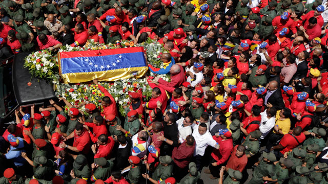 People walk alongside the flag-draped coffin containing the body of Venezuelas late President Hugo Chavez from the hospital where he died, to a military academy where it will remain until his funeral in Caracas, Venezuela, Wednesday, March 6, 2013.