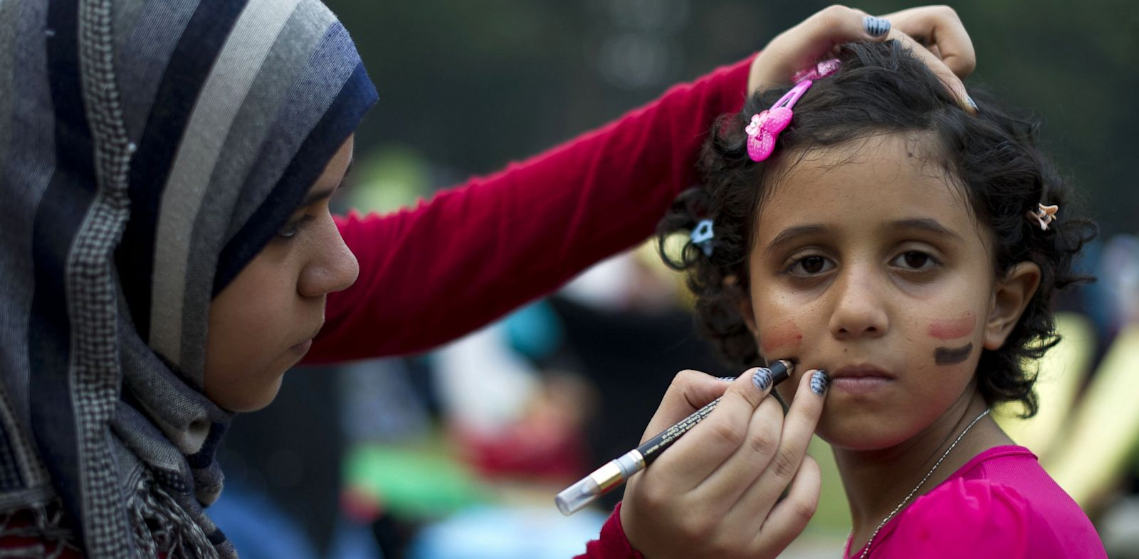 An Egyptian child sits as she has her face painted with the colors of the Egyptian national flag during a rally to oppose the military overthrow on August 17, 2013.
