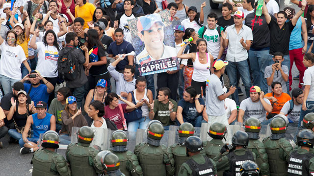 PHOTO: Opposition supporters and students, some holding pictures of opposition presidential candidate Henrique Capriles, confront riot police as they block a highway in the Altamira neighborhood of Caracas, Venezuela, Monday, April 15, 2013.