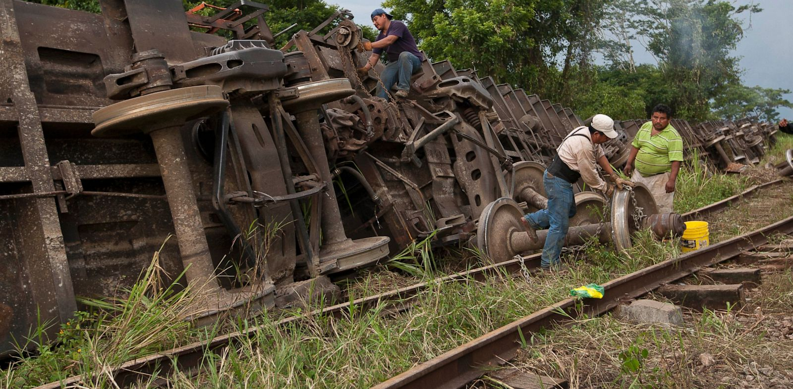 "PHOTO: Men work next to a cargo train known as ""the Beast,"" after it derailed near the town of Huimanguillo, southern Mexico, Sunday, Aug. 25, 2013."