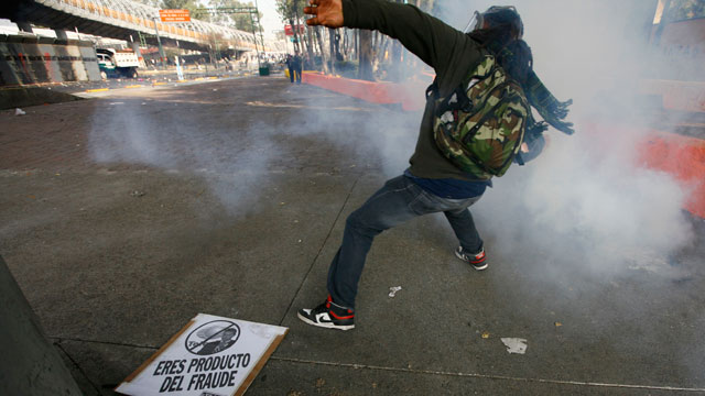 PHOTO: A demonstrator throws a stone to police during protests against new Mexican President Enrique Pena Nietos rule, outside the National Congress, in Mexico City, Saturday, Dec. 1, 2012.