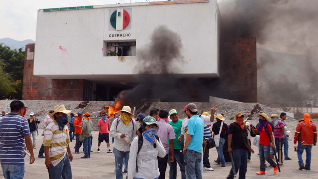 PHOTO:Protesting teachers stand outside the regional offices of the Revolutionary Institutional Party, PRI, after they attacked the building causing significant damage in Chilpancingo, Mexico, Wednesday, April 24, 2013.