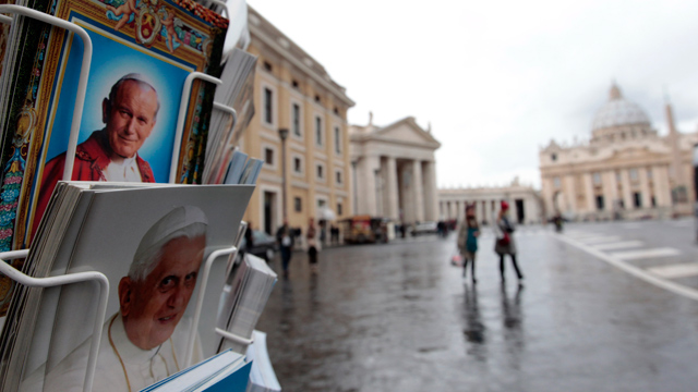 PHOTO: Postcards of Pope Benedict XVI, bottom, and late Pope John Paul II, are displayed outside a kiosk with St. Peters Basilica in the background, at the Vatican, Monday, Feb. 11, 2013.