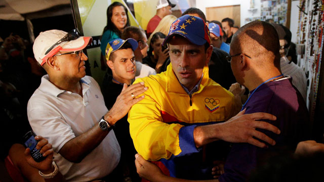 PHOTO: Venezuelan opposition candidate Henrique Capriles greets supporters who congratulate him for his victory in Miranda State on Sunday. Capriles was one of just three opposition candidates who were not defeated by Chavez allies on Sunday.