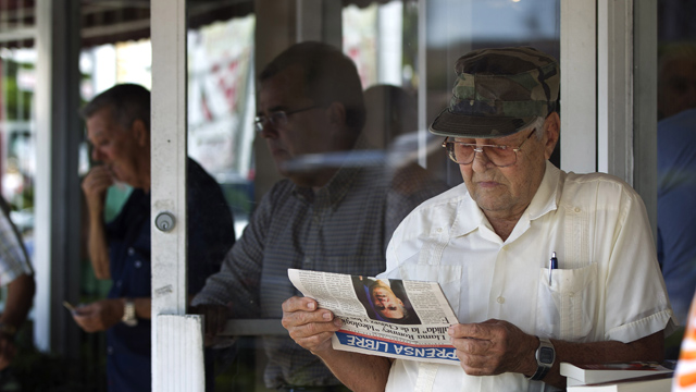 PHOTO: Nino Diaz reads a Spanish language newspaper at a Cuban cafe in Miamis Little Havana section.