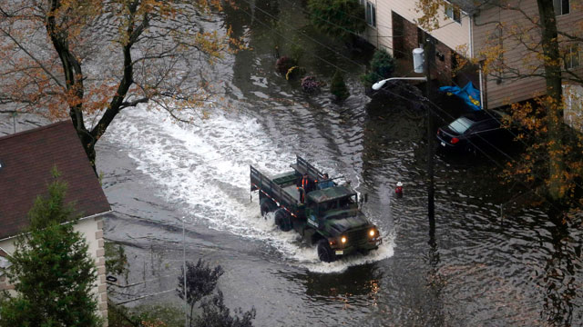 PHOTO: An emergency vehicle drives on a flooded street in Little Ferry, N.J. in the wake of superstorm Sandy on Tuesday, Oct. 30, 2012. Sandy caused multiple fatalities, halted mass transit and cut power to more than 6 million homes and businesses.