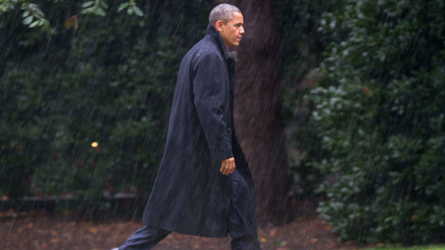 PHOTO: After canceling his appearance at a morning campaign rally in Orlando, Fla., President Barack Obama walks toward the White House in a driving rain after returning to Washington to monitor preparations for early response to Hurricane Sandy.