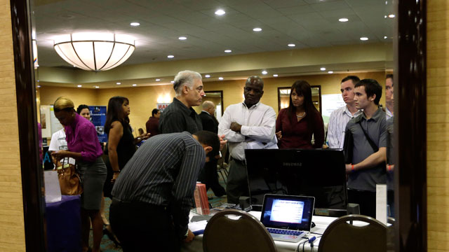 PHOTO: Robert Orkin, of the company TxT-Alert, third from left, talks with job seekers during a job fair held by National Career Fairs, in Fort Lauderdale, Fla.