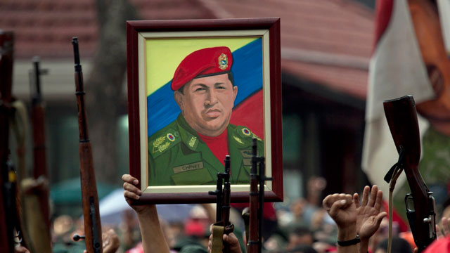 PHOTO:Members of the National Revolutionary Militia, also called Bolivarian militias, hold up their guns and a painting of Venezuelas President Hugo Chavez.