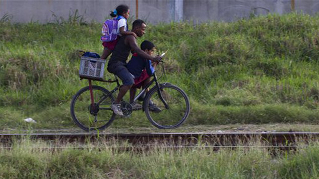 PHOTO:A man and two students ride a bicycle after leaving school in Havana, Cuba, Tuesday Nov. 20, 2012.