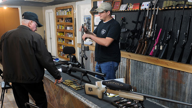 PHOTO:Clerk Lance McCoy, right, shows a variety of weapons Thursday, Dec. 20, 2012, including an AR-15 style semi-automatic at Kizer Guns and Ammo near Nacogdoches, Texas.