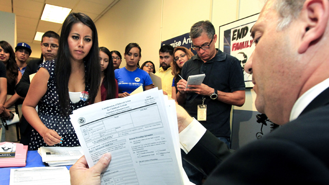 PHOTO: Young immigrants, including Gaby Perez, hand over paperwork to get guidance from immigration attorney Jose Penalosa for Obamas deferred action policy.