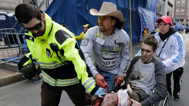 PHOTO: An emergency responder and volunteers, including Carlos Arredondo in the cowboy hat, push Jeff Bauman in a wheel chair after he was injured in an explosion near the finish line of the Boston Marathon Monday, April 15, 2013 in Boston.