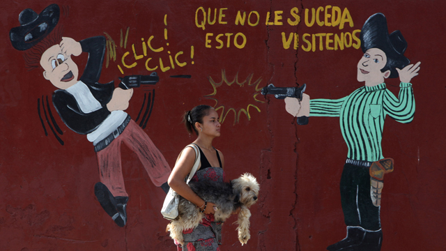 PHOTO: A woman carries her dog past an armory shop in San Pedro Sula, Honduras. Honduras has more homicides than any other country in the world with 91 per 100,000 people, the World Health Organization says.