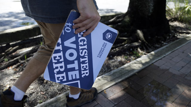 PHOTO: Matt Sagorski, a volunteer for the campaign of President Barack Obama, walks in a neighborhood with voter registration forms, Monday, Oct. 8, 2012 in Miami.