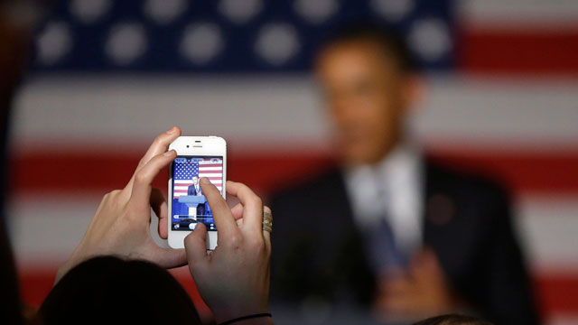 PHOTO: A member of the audience uses their cell phone to take a picture of President Barack Obama