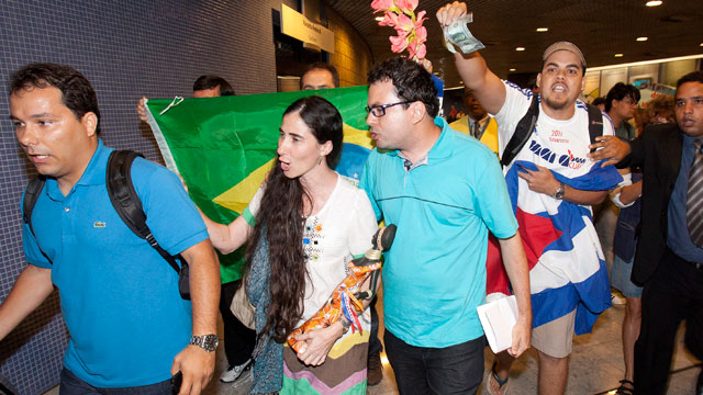 Cuban dissident blogger Yoani Sanchez, center, is chanted at by pro-Castro supporters, accusing her of being a U.S. spy, upon her arrival at the Guararapes International airport, in Recife, Brazil, Monday, Feb.18, 2013.