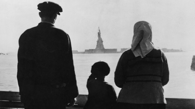 PHOTO: An immigrant family on Ellis Island looking across New York Harbor at the Statue of Liberty.