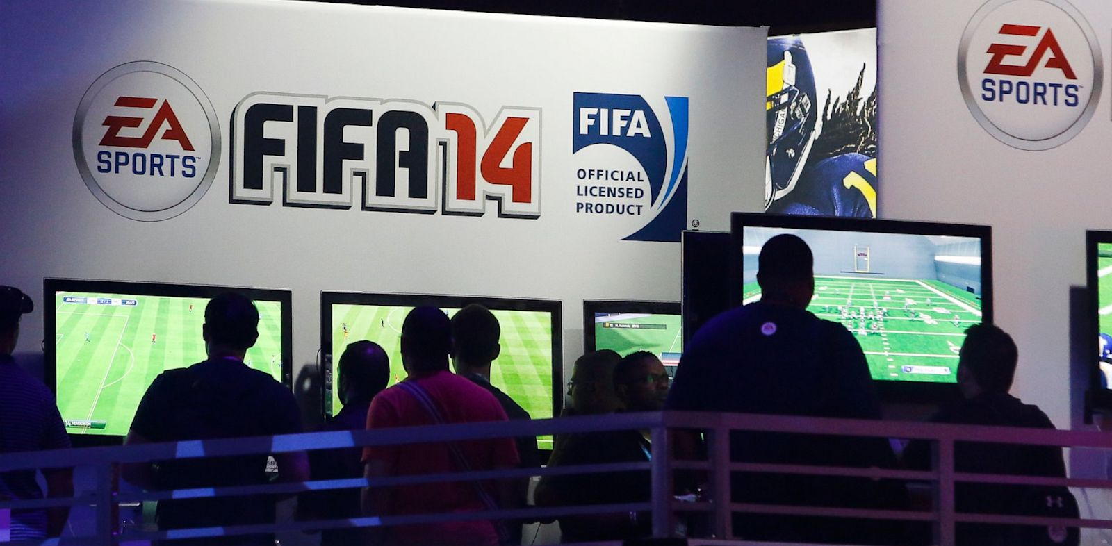 PHOTO: Attendees try out Electronic Arts Inc.s FIFA 14 and Madden NFL 25 video games at the companys booth during the E3 Electronic Entertainment Expo in Los Angeles, California, U.S., on Wednesday, June 12, 2013.