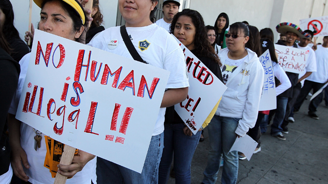PHOTO:OAKLAND, CA - APRIL 30: People with the group 'Youth United For Justice' hold signs in protest of Arizona's immigration law.