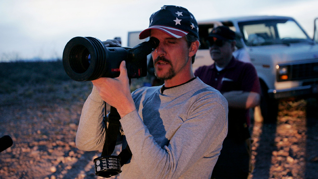 PHOTO:Chris Simcox, one of the organizers of the Minuteman Project, looks through an infrared scope trying to spot people moving towards the United States border April 2, 2005 near Naco, Arizona.