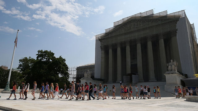 PHOTO:Tourists walk out in front of the U.S. Supreme Court building June 17, 2013 in Washington DC. Today the high court ruled 7-2 to throw out Arizonas proof of citizenship voter registration requirement.