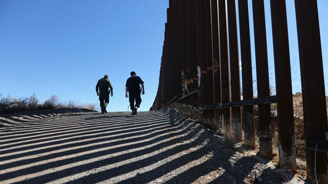 PHOTO: U.S. Customs and Border Protection personnel walk along a section of the recently-constructed fence at the U.S.-Mexico border on February 26, 2013 in Nogales, Arizona.
