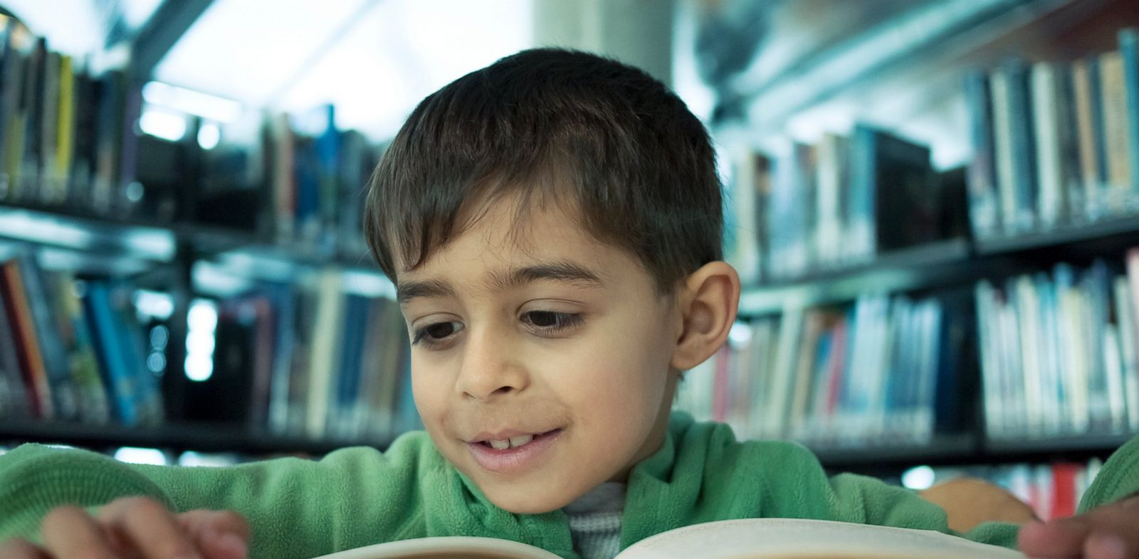 Boy reads book in public library