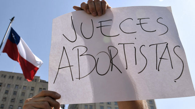 PHOTO: A Chilean man shows a poster (reading: Pro-Abortion Judges)
