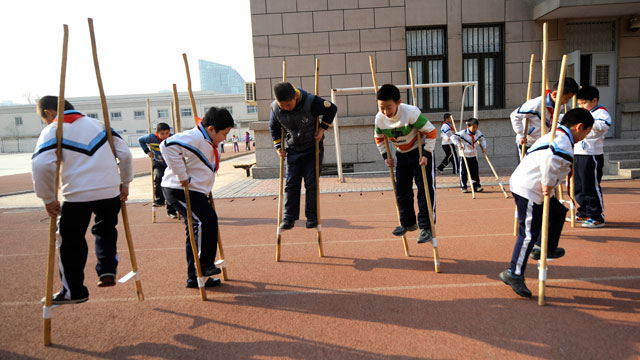 PHOTO: Pupils practice stilt walking during a sports lesson at a primary school in Beijing on January 10, 2011.