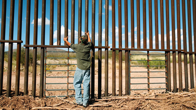 PHOTO: A man stands at a border fence between the United States and Mexico.