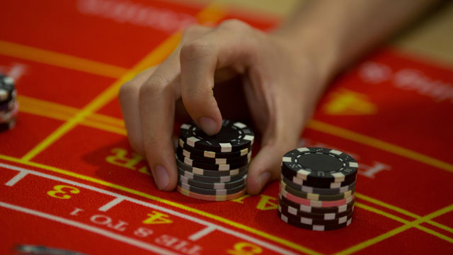 PHOTO: A student handles gaming chips during a demonstration at a blackjack table at the Macao Polytechnic Institute (MPI) Gaming Teaching and Research Centre in Macau, China, on Tuesday, June 18, 2013.