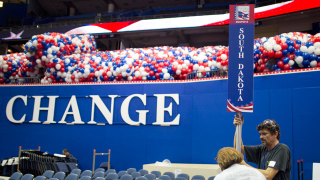 PHOTO: Workers set up state placards for delegates in preparation for the Republican National Convention (RNC) inside the Tampa Bay Times Forum in Tampa, Florida, U.S., on Friday, Aug. 24, 2012.
