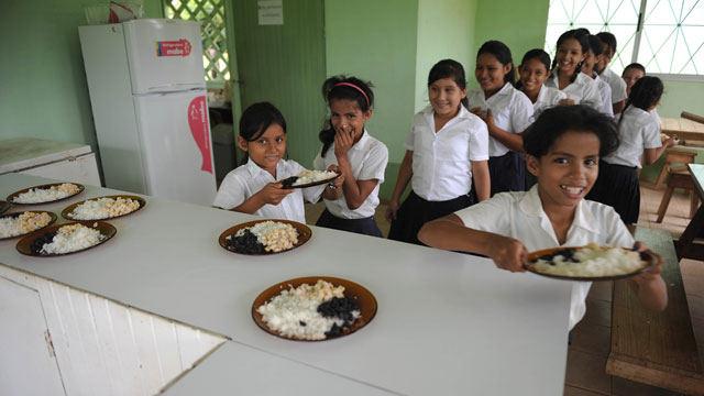 PHOTO: Schoolchildren take a meal at Las Crucitas primary school near 'Las Crucitas Camp.'
