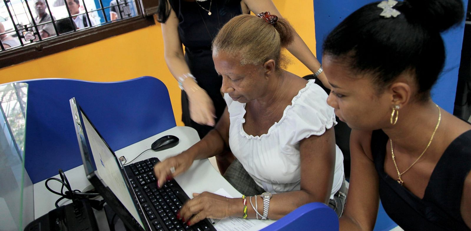 PHOTO: An employee of ETECSA (Cuban telecommunications company) helps a client at a cyber place in Havana on June 4, 2013.