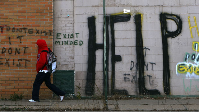 PHOTO: A pedestrian walks by graffiti on a downtown street November 20, 2008 in Detroit, Michigan. Detroit became the largest city in the United States to file for bankruptcy on Thursday, July 18, 2013.