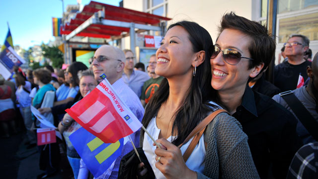 PHOTO:Jenni Chang (L) and Lisa Dazols (R) look on as celebrations ensue in the Castro neighborhood of San Francisco, California, June 26, 2012, after the US Supreme Court struck down The Defense of Marriage Act (DOMA).