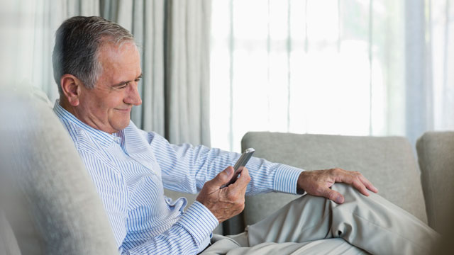 PHOTO: Older man using cell phone on sofa