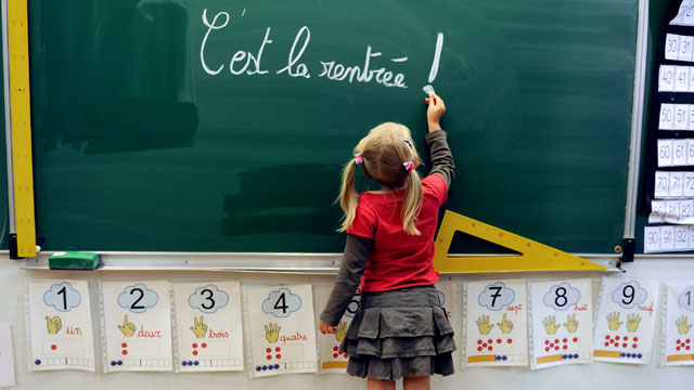PHOTO: A little girl writes on the blackboard 'C'est la rentrée' (Its the Start of the school year) at the school Jules Ferry in Bethune, northern, France, on August 28, 2012.