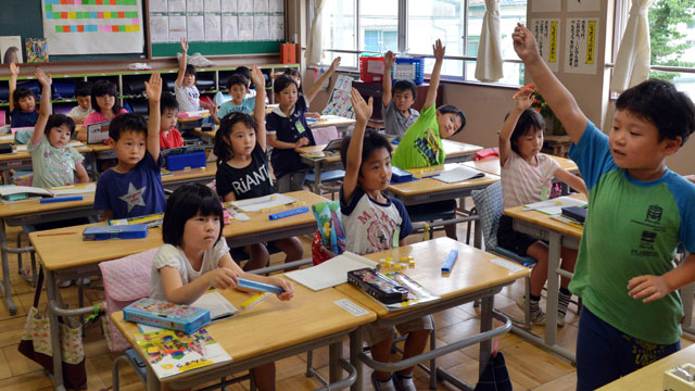 PHOTO: Six-year-old Japanese elemetary student Seishi Nishida (2nd row L blue shirt) raises his hand along with classmates at school in Tokyo on June 11, 2013.