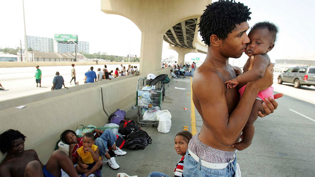 PHOTO: Daryl Thompson holds his 3-month old daughter Dejanae as they wait with other displaced residents on a highway in the hopes of catching a ride out of town August 31, 2005 in New Orleans.
