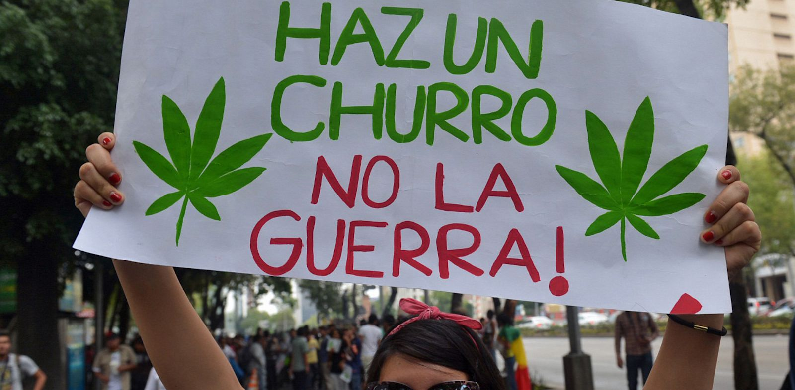 "PHOTO: A woman holds a baner reading ""Make a joint, not war"" during a demo in support of the legalization of marijuana, in Mexico City."