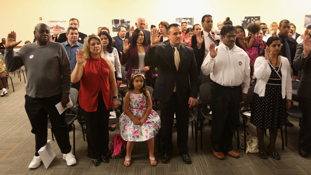 PHOTO: Immigrants take the oath of citizenship at a special Valentines Day naturalization ceremony for married couples on February 14, 2013 in Tampa, Florida.