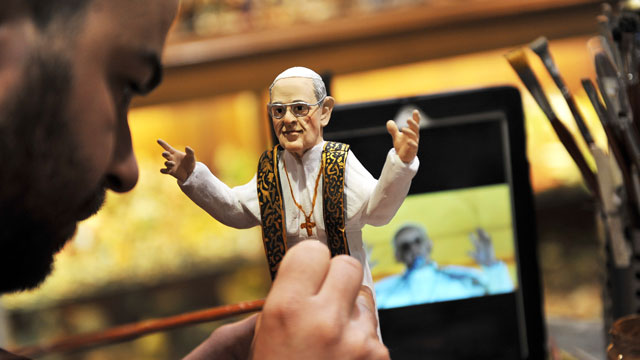 PHOTO: Artisan Genny Di Virgilio paints a hand-crafted figurine of Pope Francis.