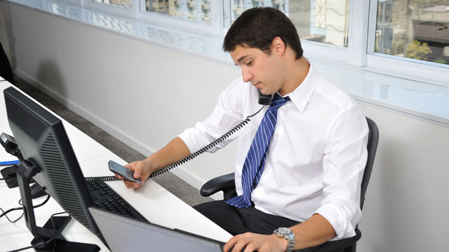 PHOTO:A man multitasks at an office.