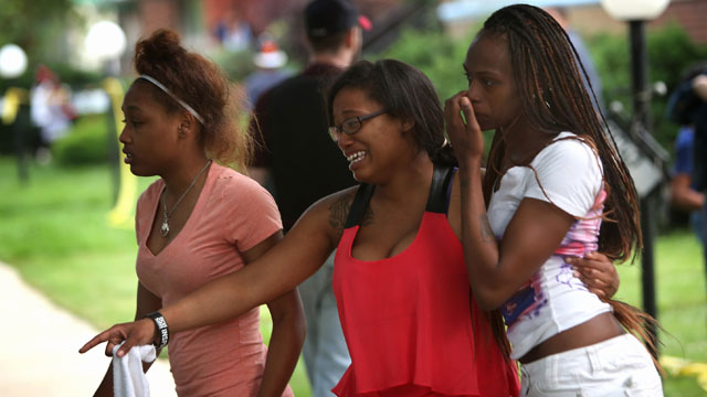 PHOTO: Young women watch as police prepare to remove the remains of their friend after he was shot and killed on June 22, 2013 in Chicago, Illinois.