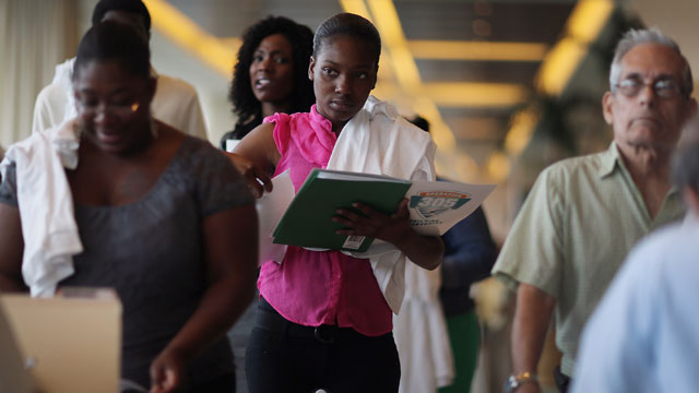 PHOTO: Sandra Bonham (C) and other people looking for work stand in line to apply for jobs during a job fair at the Miami Dolphins Sun Life stadium on May 2, 2013 in Miami, Florida.