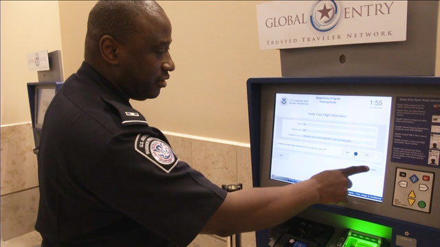 PHOTO: A Customs and Border Protection official demonstrates a Global Entry kiosk at John Wayne Airport.