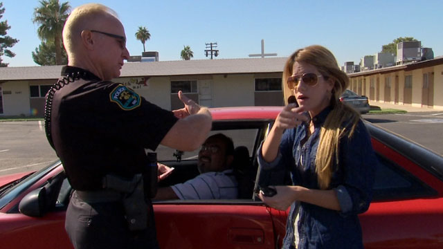 """Univisions reporter Andrea Sambuccetti talks to an officer in Phoenix, Arizona, after her producer was pulled over for """"impeding traffic""""."""