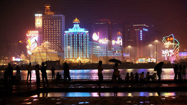 PHOTO: People walk on a water front near a strip of casinos at night in Macau.